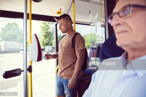 passenger paying fare through contactless payment - fare stock pictures, royalty-free photos & images