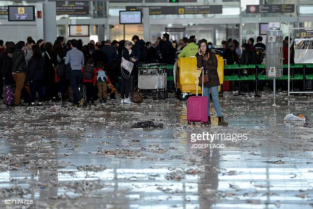 A passenger phones in a hall of BarcelonaEl prat aiport littered with pieces of paper and rubbish during a strike of the airport cleaning staff in El...