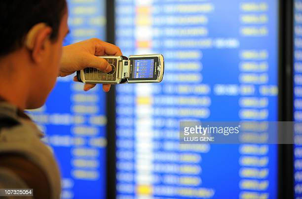 A passenger pictures electronic boards announcing cancelled flights on December 4 2010 as he waits at the El Prat airport near Barcelona Spain's...