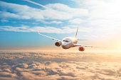 Passenger plane, business trip, travel concept. Flying evening sunset.