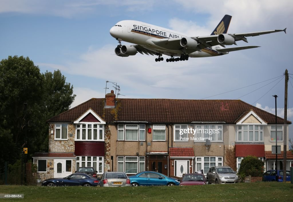 A passenger plane comes into land near housing at Heathrow Airport on August 11, 2014 in London, England. Heathrow is the busiest airport in the United Kingdom and the third busiest in the world. The airport's operator BAA wants to build a third runway to cope with increased demand.