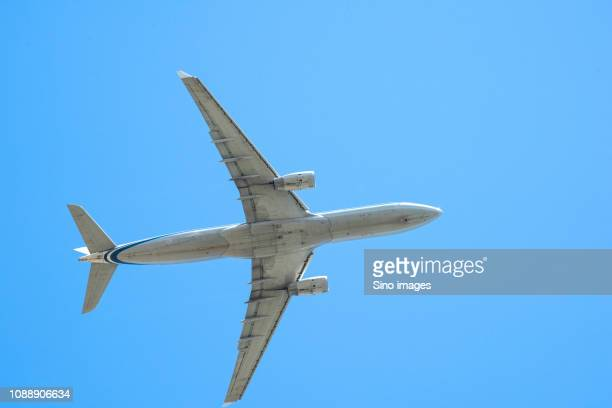 passenger plane flying on clear blue sky, beijing, china - image stockfoto's en -beelden