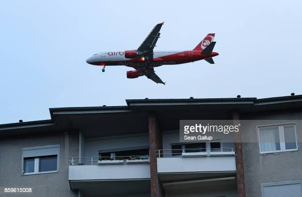 A passenger plane of Air Berlin flies over a residential district shortly before its arrival at Tegel airport on October 9 2017 in Berlin Germany The...