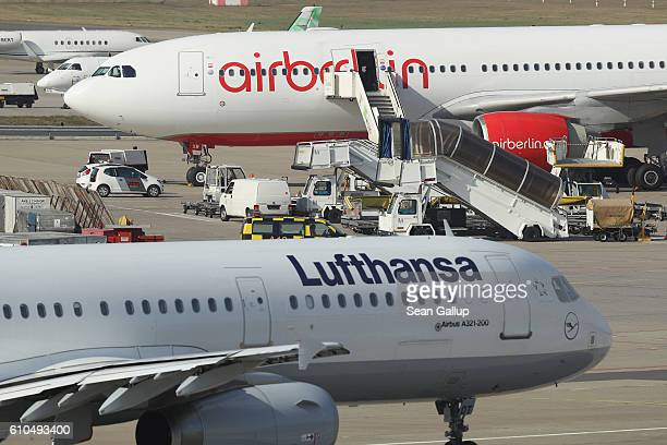 A passenger plane of German airliner Lufthansa passes by one of Air Berlin on the tarmac at Tegel Airport on September 26 2016 in Berlin Germany...