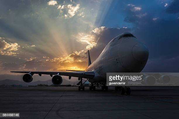 Passenger plane on taxiway at sunset