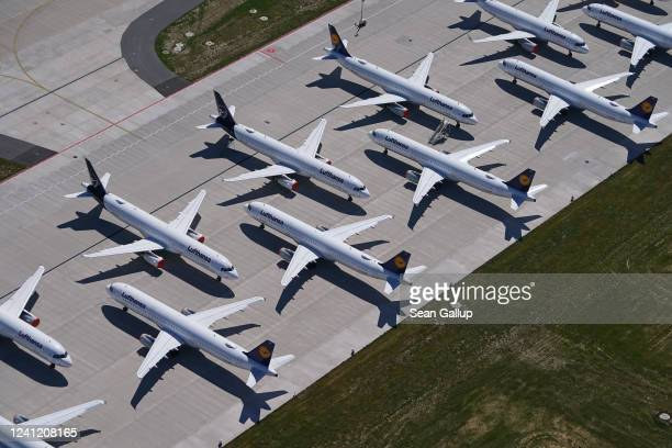 Passenger planes of airline Lufthansa that have been temporarily pulled out of service stand parked at Berlin-Brandenburg Airport during the...