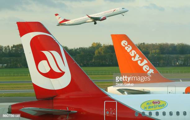 Passenger planes of airliners Air Berlin and easyJet stand at Vienna Airport as an Austrian Airlines plane takes off behind on October 13 2017 in...