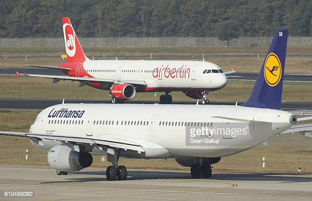 Passenger planes of German airliners Air Berlin and Lufthansa pass one another on the tarmac at Tegel Airport on September 26 2016 in Berlin Germany...