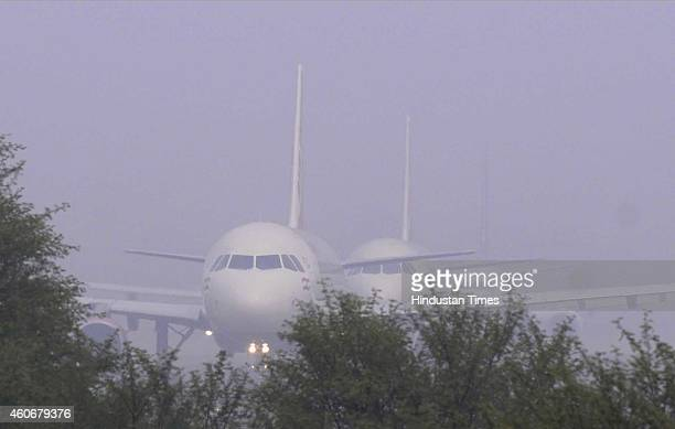 Passenger planes wait at the Runway of Indira Gandhi International Airport to take off in a dense foggy morning on December 18 2014 in New Delhi...