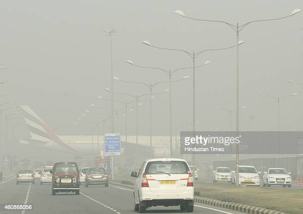 Passenger planes wait at the Runway of Indira Gandhi International Airport to take off in a dense foggy morning on December 28 2014 in New Delhi...