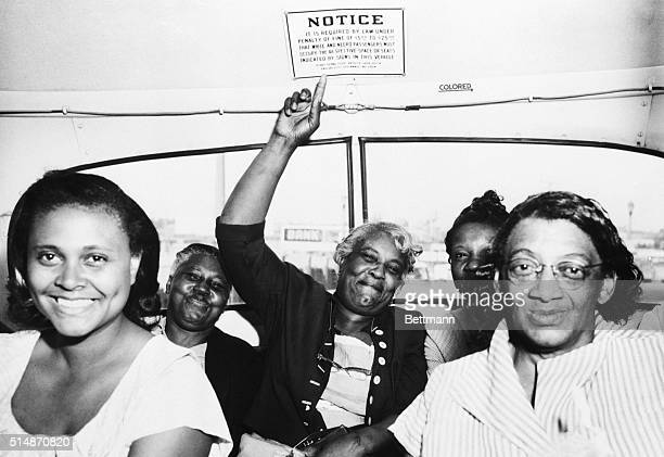 A passenger points to one of the segregation signs removed from all Dallas Transit Company buses following a Supreme Court ruling banning segregation...