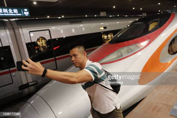 Passengers walk past a GuangzhouShenzhenHong Kong Express Rail Link Vibrant Express train operated by MTR Corp after it arrives at West Kowloon...