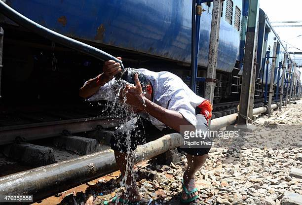 A passenger pours water from a hose pipe on his head to cool off during a hot day at the Allahabad junction The death toll from the blistering heat...