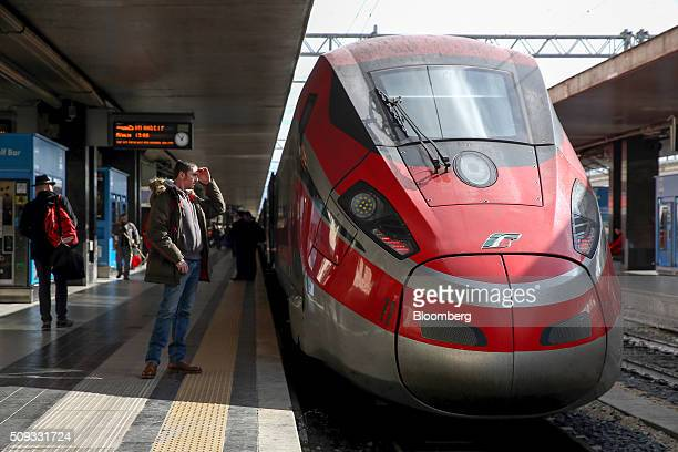 A passenger prepares to board a Freccia Rossa 1000 highspeed train operated by Trenitalia SpA at Termini railway station in Rome Italy on Tuesday Feb...