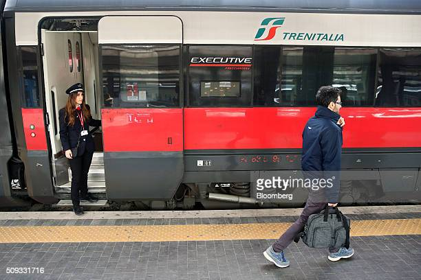 A passenger prepares to board a Freccia Rossa highspeed train operated by Trenitalia SpA at Termini railway station in Rome Italy on Tuesday Feb 9...