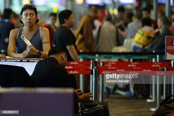 A passenger prepares to checkin at AirAsia counter at Changi Airport Terminal 1 on December 29 2014 in Singapore AirAsia announced that flight QZ8501...