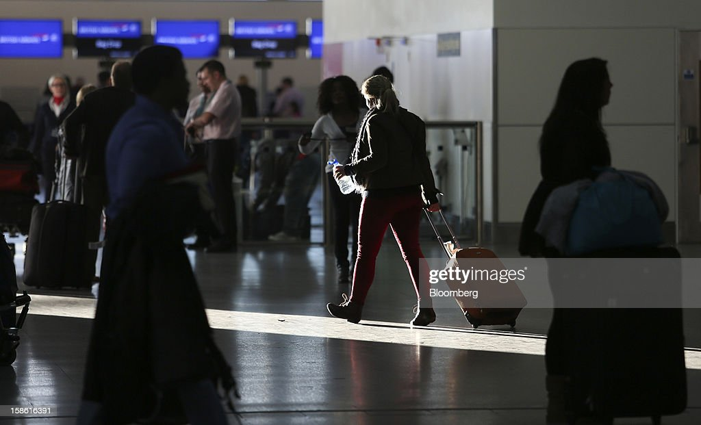 A passenger pulls her suitcase as she walks through the check-in area of the north terminal at Gatwick airport in Crawley, U.K., on Friday, Dec. 21, 2012. U.K. airports predicted today to be the busiest day during the Christmas period, as some Britons opt to spend the holidays abroad and overseas visitors fly out to be with friends and family. Photographer: Chris Ratcliffe/Bloomberg via Getty Images