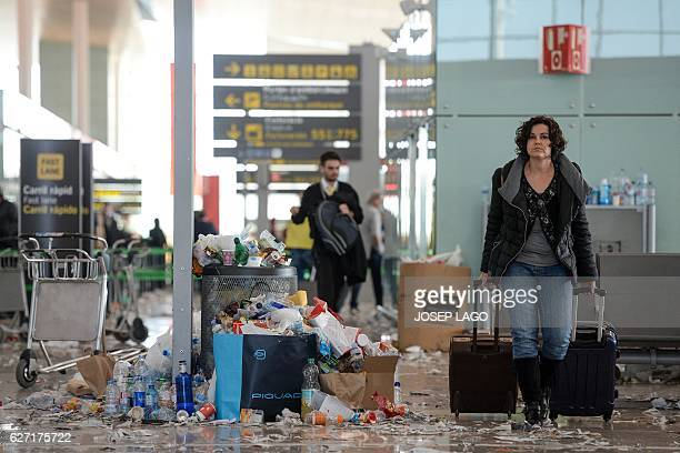 A passenger pulls two trolleys in a hall of BarcelonaEl prat aiport littered with pieces of paper and rubbish during a strike of the airport cleaning...