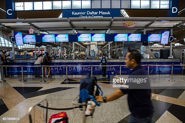 A passenger pushes a cart past ticket counters for Malaysian Airlines Bhd at Kuala Lumpur International Airport in Sepang Selangor Malaysia on...