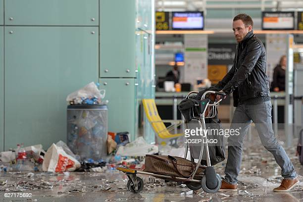 A passenger pushes a trolley in a hall of BarcelonaEl prat aiport littered with pieces of paper and rubbish during a strike of the airport cleaning...