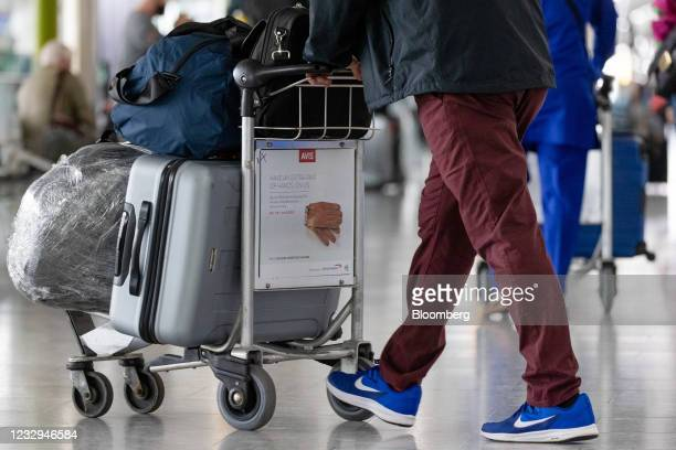 Passenger pushes a trolley of luggage wait in the departures hall in Terminal 5 at London Heathrow Airport in London, U.K., on Monday, May 17, 2021....