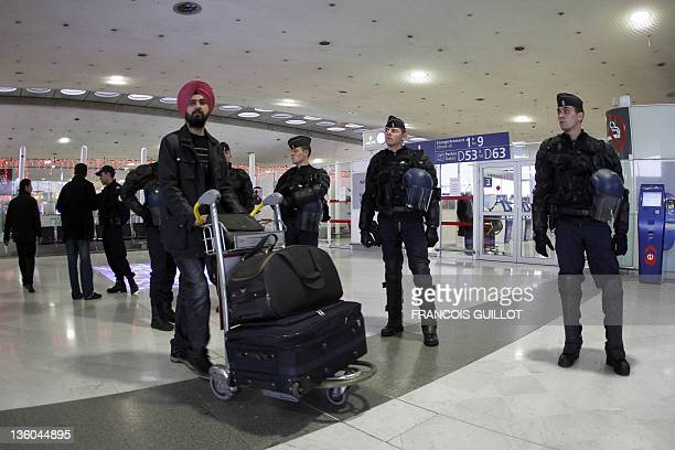 A passenger pushes his luggage trolley in front of antiriot policemen who are protecting a boarding gate during a demonstration held by striking...