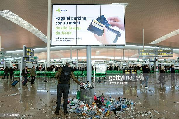 A passenger puts an object in a rubbish bin surrounded by pieces of paper and rubbish in a hall of BarcelonaEl prat aiport during a strike of the...