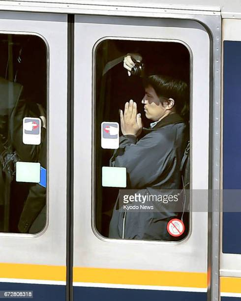 A passenger puts his hands together in prayer inside a train in Amagasaki Hyogo Prefecture western Japan on April 25 the 12th anniversary of a...