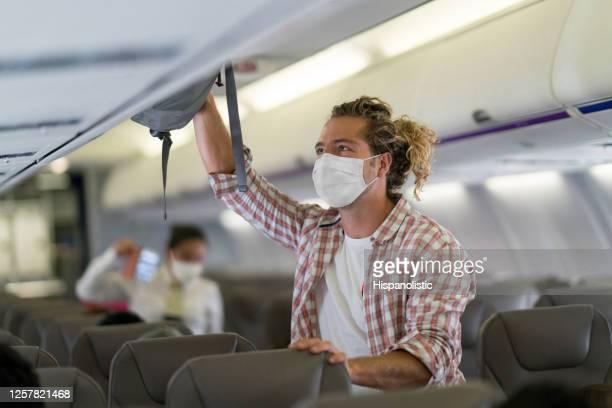 passagier legt sein handgepäck in den gepäckraum und trägt eine gesichtsmaske - lateinamerika stock-fotos und bilder