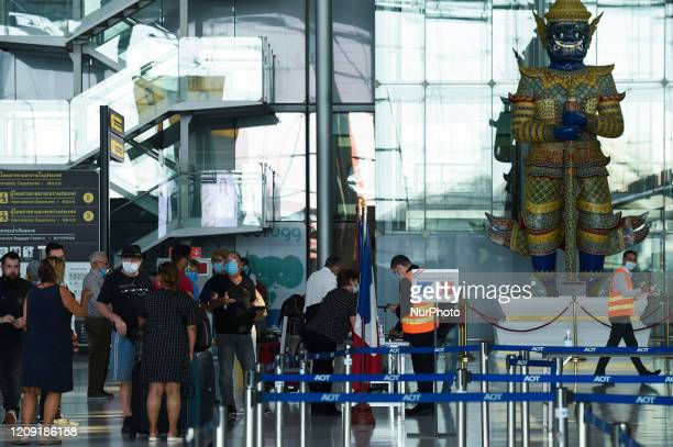 Passenger queue up at the check-in counter after several airlines suspended their flight operations, at Suvarnabhumi Airport, Samut Prakan province,...