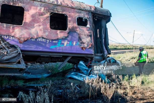 A Passenger Rail Agency South Africa inspector looks at the wreckage of a car which was being transported in a train after an accident near Kroonstad...