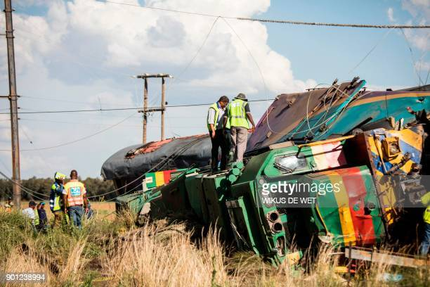 Passenger Rail Agency South Africa inspectors look at a derailed train locomotive after an accident near Kroonstad in the Free State Province some...