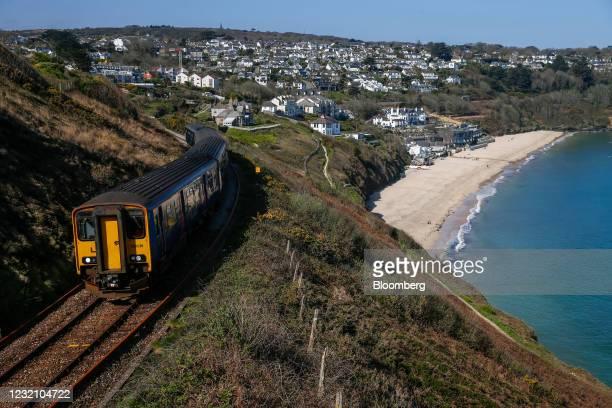 Passenger railway train passes along the coastline in view of Carbis Bay Hotel & Estate in Cornwall, U.K., on Sunday, April 4, 2021. U.K. Prime...