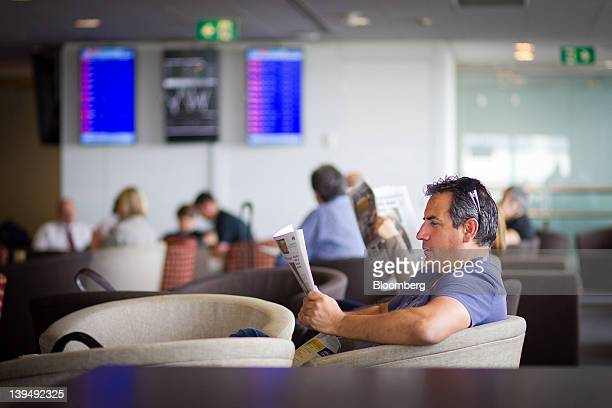 A passenger reads a newspaper in the Virgin Australia Holdings Ltd lounge at the domestic terminal of Sydney airport in Sydney Australia on Wednesday...