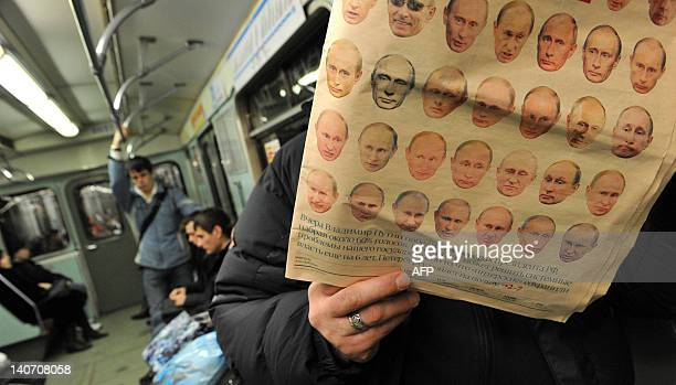 A passenger reads a paper featuring images of different face expressions of Russia's Prime Minister Vladimir Putin while riding in a subway carriage...
