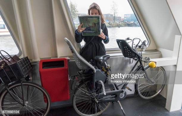 A passenger reads the newspaper onboard a ferry sailing to Central Station from NDSM on April 21 2017 in Amsterdam Netherlands GVB ferries crisscross...