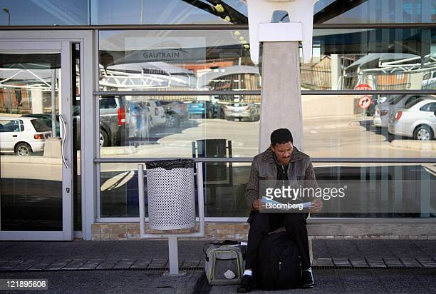 A passenger reads while waiting outside Gautrain's Marlboro mass transit rail station in Johannesburg South Africa on Monday Aug 22 2011 South Africa...