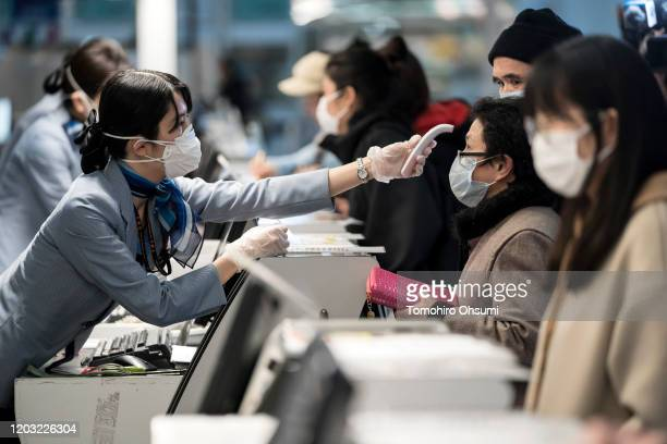 A passenger receives a temperature check before taking a flight bound for Wuhan at Spring Airlines' checkin counter at Haneda airport on January 31...