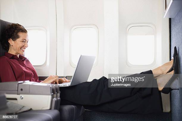 Passenger relaxing with laptop computer on airplane