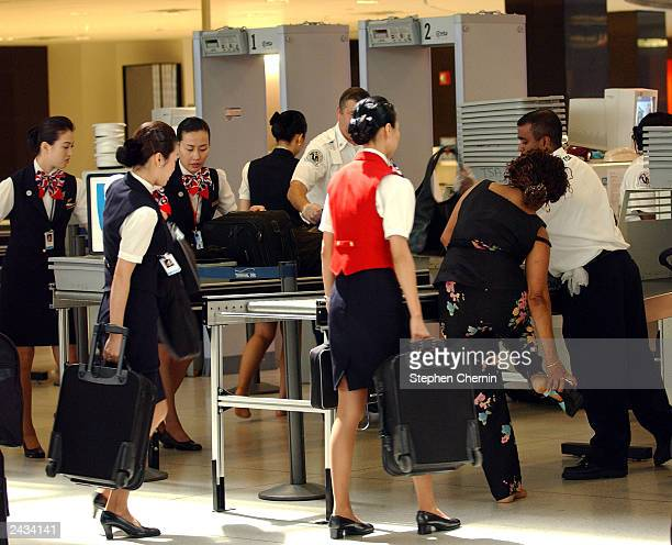 A passenger removes her shoe as Korean Airline stewardesses queue up to pass through the metal detector at a security checkpoint at John F Kennedy...