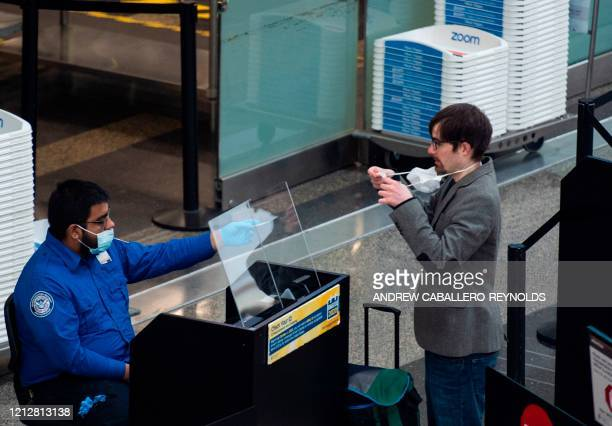 Passenger removes his mask as he has his ID checked by a Transportation Security Administration employee in Ronald Reagan Washington National Airport...
