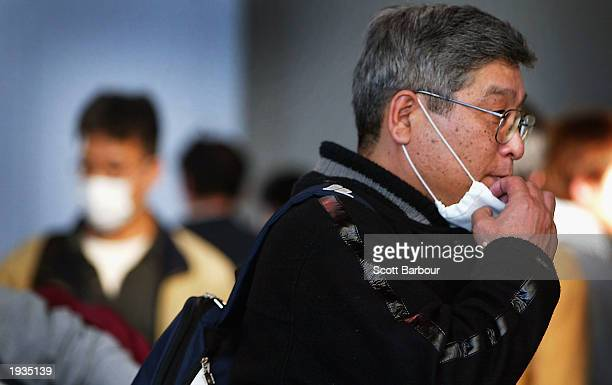 A passenger removes his surgical mask which he wore to protect against the SARS virus as he arrives at Heathrow Airport April 16 2003 in London...