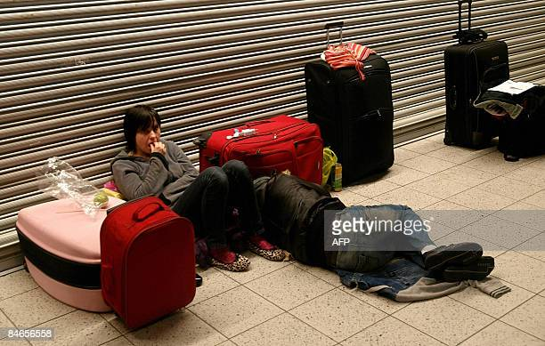 Passenger rest on the floor at Luton Airport north London on February 5 2009 Heavy snowfalls brought fresh chaos to large parts of Britain on...