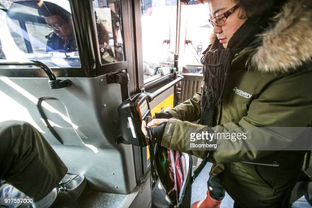 A passenger scans a wallet containing a Cashbee transportation card operated by EB Card Co a unit of Lotte Corp onboard a bus in Seoul South Korea on...