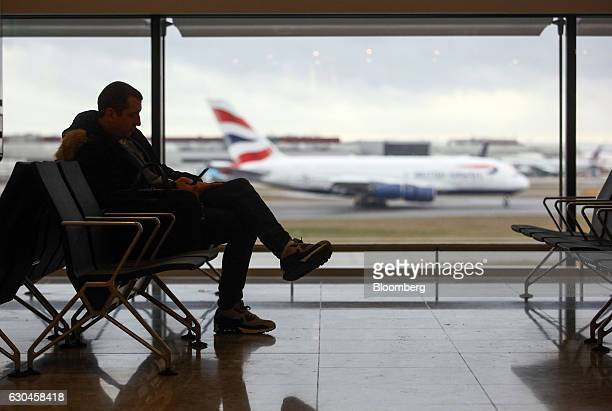 A passenger sits at a departure gate against a backdrop of a British Airways aircraft landing at terminal 2 at London Heathrow Airport in London UK...
