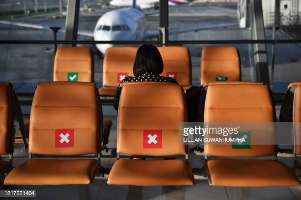 A passenger sits in sociallydistanced seats at the gates in a nearempty Suvarnabhumi International Airport in Bangkok on June 3 as domestic Thai...