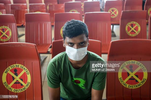 Passenger sits next to signs requesting to maintain social distancing as a preventive measure against the spread of the COVID-19 coronavirus at the...