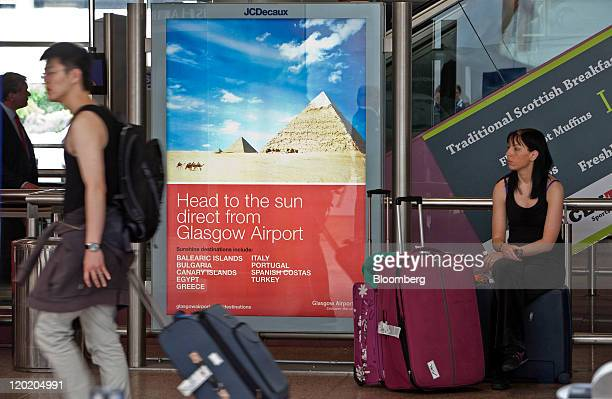 A passenger sits with luggage near a JC Decaux SA advertisment at BAA Ltd's Glasgow airport in Glasgow Scotland on Friday July 29 2011 BAA Ltd was...