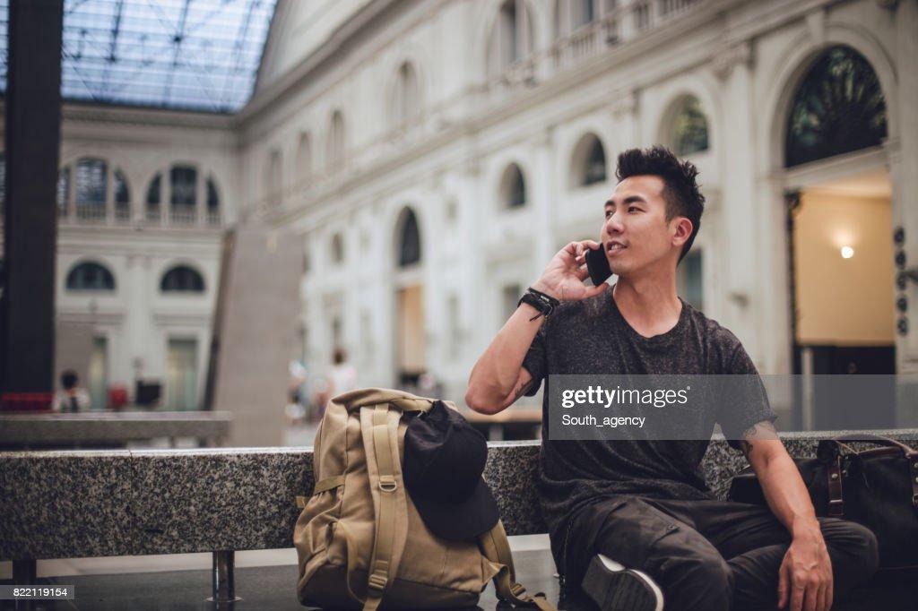 Passenger sitting at train station and using phone : Stock Photo