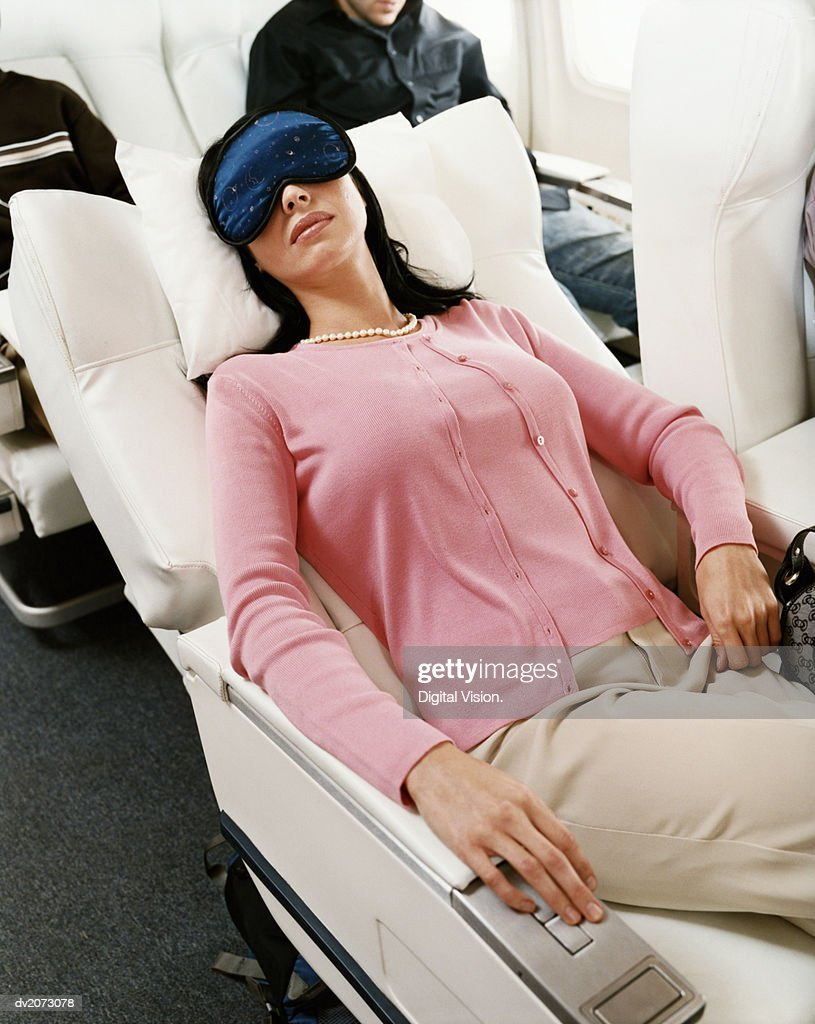 Passenger Sleeping in an Aircraft Cabin Interior : Stock Photo